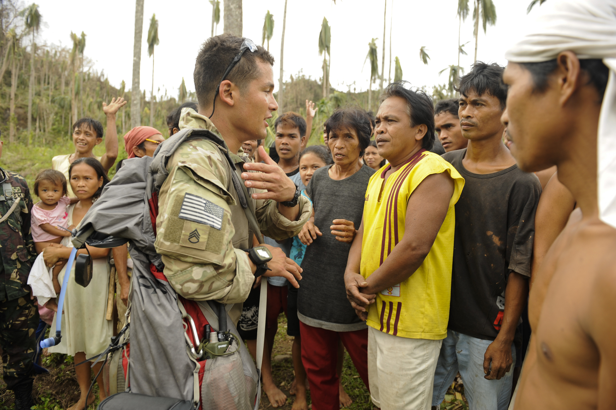 Staff Sgt. Andrew Guingona from the 1st Special Forces Group, A Company, 4th Battalion, talks with residents about receiving relief supplies from a US Navy helicopter from HSC-12 on Wednesday, November 20, 2013. Guingona said by bringing Filipino aid workers and soldiers, it helped maintain order at a supply drop. (Mike Morones/Staff)