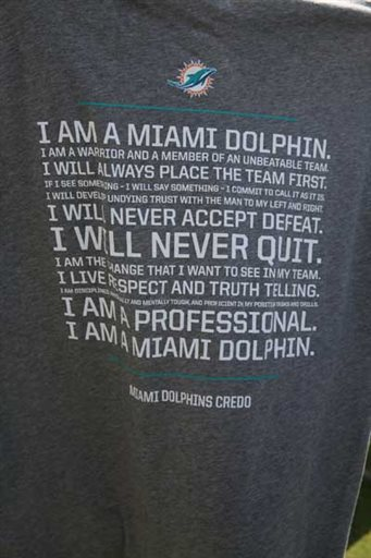 A T-shirt is displayed at the Miami Dolphins NFL football training camp in Davie, Fla., Wednesday, July 30, 2014. The Dolphins, rocked by a bullying scandal last season, are now wearing T-shirts bearing a credo of togetherness that was coined by the players. (AP Photo/The Miami Herald, Walter Michot)
